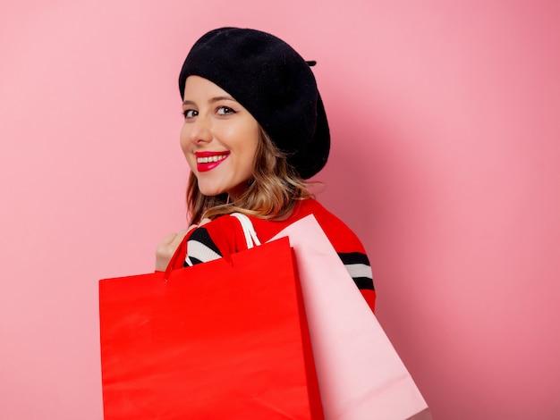 Piękna kobieta z torba na zakupy na menchii ścianie Premium Zdjęcia