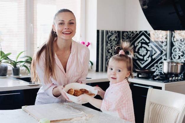 Piękna Kobieta Z Uroczym Dziecka Mienia Pucharem Z Ciastkami Premium Zdjęcia