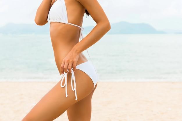 Piękna kształt kobieta w białym bikini swimsuit pozuje przy plażą Premium Zdjęcia
