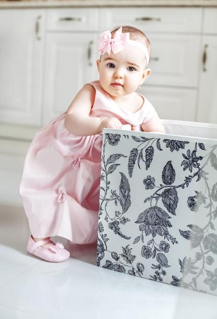 Piękna Laska Dostaje Zabawki Z Pudełka. Różowa Sukienka. Premium Zdjęcia
