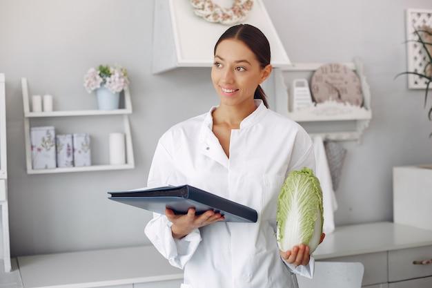 Piękna lekarka w kuchni z warzywami Darmowe Zdjęcia