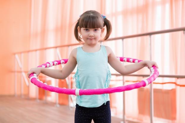 Piękna mała dziewczynka robi sportom. Premium Zdjęcia