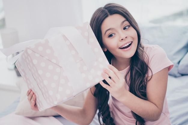Piękna Mała Dziewczynka Siedzi Na łóżku Z Dużym Pudełkiem Premium Zdjęcia