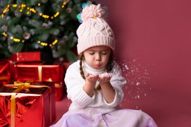 Piękna mała dziewczynka w kapeluszu bawić się z śnieżnymi pobliskimi teraźniejszość i choinką Premium Zdjęcia