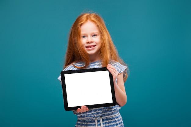 Piękna mała dziewczynka w koszulce z długimi włosami trzymać tablet Premium Zdjęcia