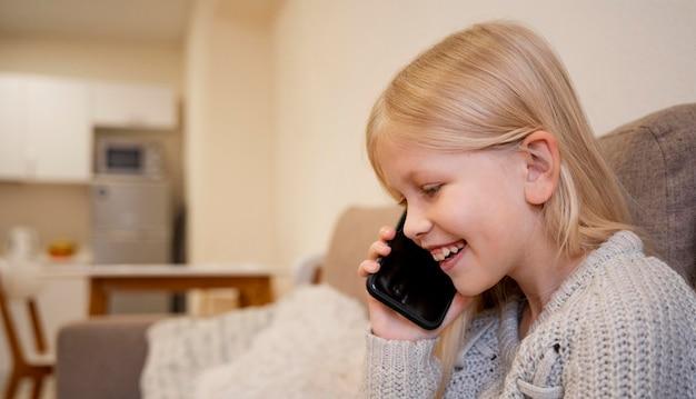 Piękna Mała Dziewczynka Z Smartphone W Domu Darmowe Zdjęcia