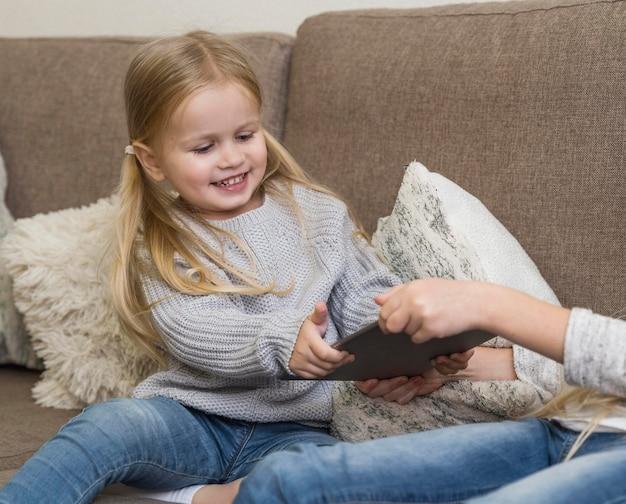 Piękna Mała Dziewczynka Z Tabletem W Domu Darmowe Zdjęcia