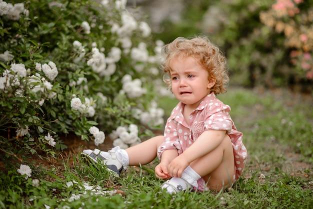 Piękna Mała Dziewczynka Z Uczciwym Kędzierzawym Włosy Na Spacerze W Parku W Ciepłym Letnim Dniu Premium Zdjęcia