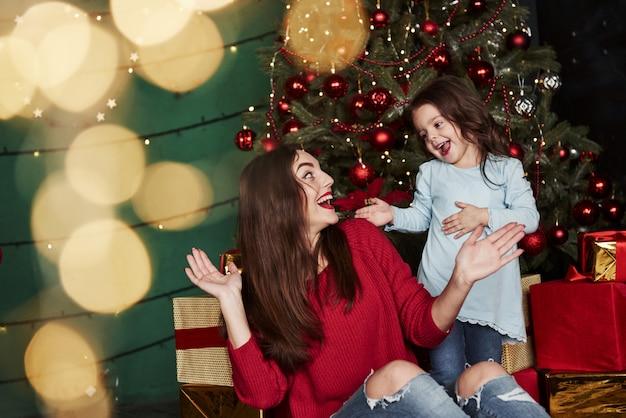 Piękna Matka Bawi Się Z Córką W Przepięknie Urządzonym Pokoju Z Choinką Premium Zdjęcia