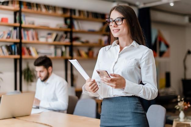 Piękna millenial biznesowa kobieta z telefonem w biurze Premium Zdjęcia