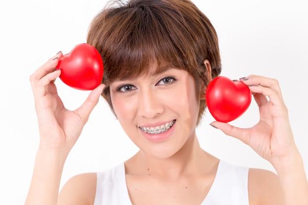Piękna młoda asia kobieta z czerwonymi sercami. Premium Zdjęcia