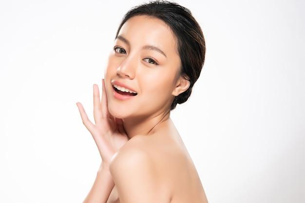 Piękna młoda azjatycka kobieta dotyka miękkiego policzek i uśmiech z czystą i świeżą skórą. szczęście i radość, na białym tle, piękno i kosmetyki, Premium Zdjęcia