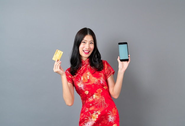 Piękna Młoda Azjatycka Kobieta Nosi Czerwoną Chińską Sukienkę Za Pomocą Smartfona I Trzyma Kartę Kredytową Premium Zdjęcia