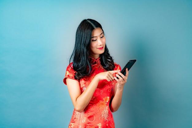 Piękna Młoda Azjatycka Kobieta Nosi Czerwoną Chińską Sukienkę Za Pomocą Smartfona Premium Zdjęcia