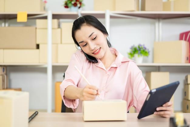 Piękna Młoda Azjatycka Kobieta Sprzedaje Produkty Online. ładna Azjatycka Dziewczyna Pisze Adresie Pocztowym Na Papierowym Pakuneczka Pudełku. Premium Zdjęcia