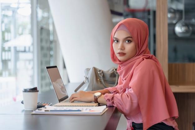 Piękna Młoda Azjatykcia Muzułmańska Biznesowa Kobieta W Różowym Hijab I Przypadkowej Odzieży Pracuje Z Laptopem Premium Zdjęcia