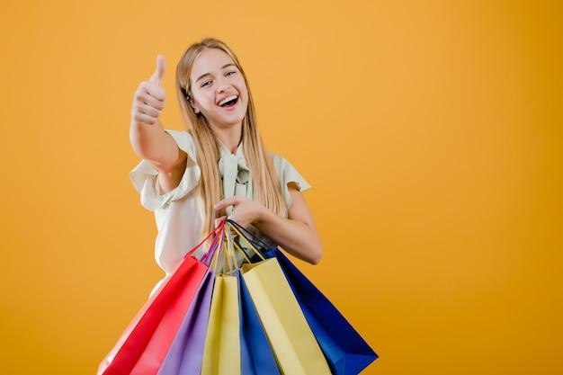 Piękna młoda blondynki kobieta ono uśmiecha się z kolorowymi torba na zakupy odizolowywającymi nad kolorem żółtym Premium Zdjęcia
