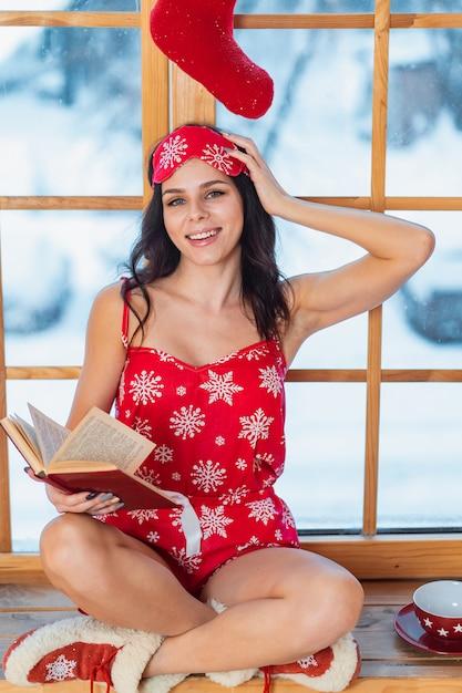 Piękna Młoda Brunetki Kobieta Jest Ubranym Czerwoną Piżamę I Czyta Okno Darmowe Zdjęcia
