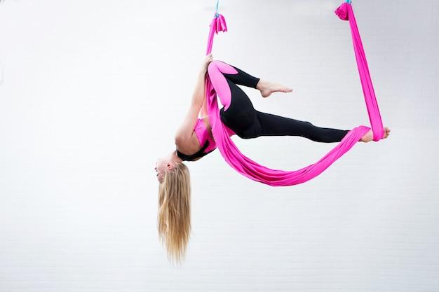Piękna młoda dziewczyna joga antygrawitacyjna na różowym jedwabnym hamaku podczas wykonywania. Premium Zdjęcia