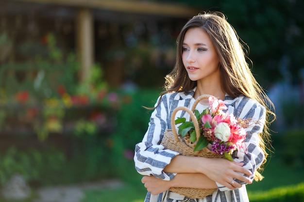 Piękna Młoda Dziewczyna O Długich, Zdrowych Włosach W Pasiastym Garniturze Idzie Ulicą I Trzyma W Ręce Wiklinową Torbę Z Kwiatami. Pojęcie Stylu życia. Młodość I Szczęście. Premium Zdjęcia