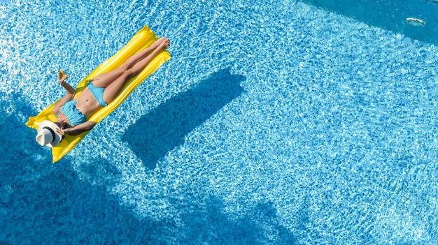 Piękna młoda dziewczyna relaks w basenie, pływa na nadmuchiwanym materacu i dobrze się bawi w wodzie na rodzinne wakacje, tropikalny ośrodek wypoczynkowy, widok z lotu ptaka z drona Premium Zdjęcia