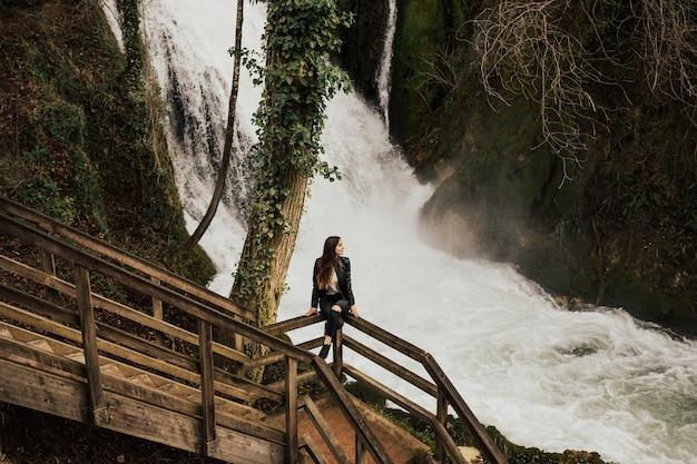 Piękna, Młoda Dziewczyna Siedzi W Pobliżu Niesamowitego Wodospadu W Terni We Włoszech. Premium Zdjęcia