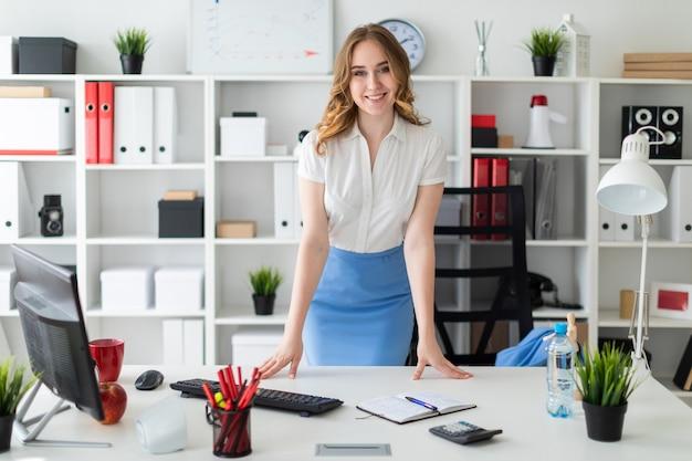 Piękna Młoda Dziewczyna Stoi W Biurze Z Rękami Na Stole. Premium Zdjęcia