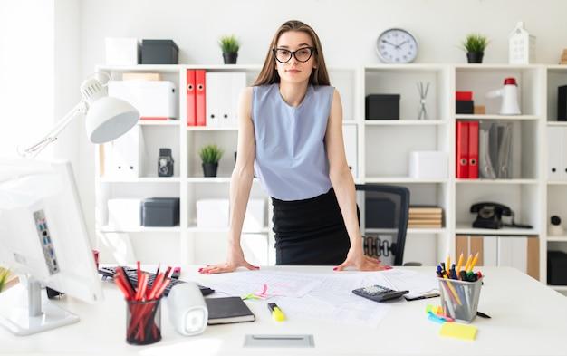 Piękna Młoda Dziewczyna W Biurze Stoi Przy Stole I Wkłada Ręce. Premium Zdjęcia