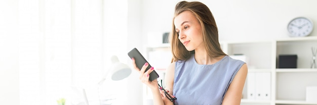 Piękna Młoda Dziewczyna W Biurze Stoi Przy Stole, Trzyma W Dłoni Okulary I Patrzy Na Ekran Telefonu. Premium Zdjęcia