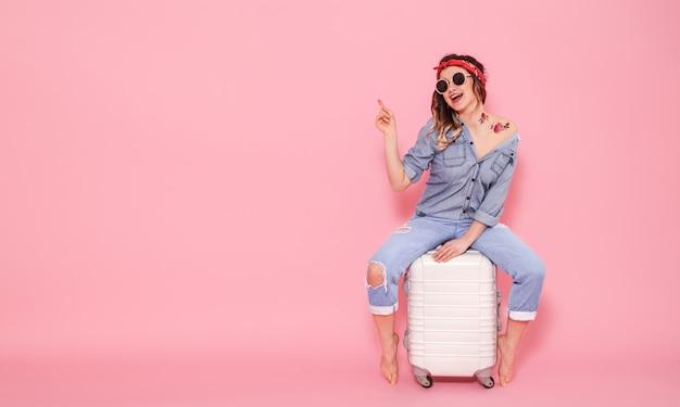 Piękna Młoda Dziewczyna W Dżinsowej Koszuli Z Naklejką Wodną Tatuaż Kwiaty Naklejka Uśmiecha Się I Siedzi Na Walizce Premium Zdjęcia