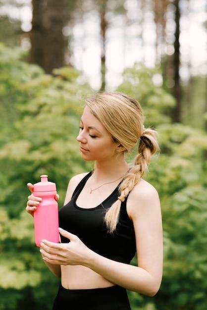 Piękna, Młoda Dziewczyna W Mundurze Sportowym Z Butelką Wody, Joga I Sporty W Lesie Na świeżym Powietrzu Premium Zdjęcia
