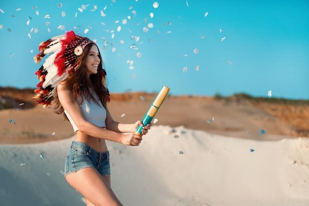 Piękna Młoda Kaukaska Dziewczyna W Białej Bluzce I Jeansowych Szortach Na Głowie Ma Na Sobie Indyjski Kapelusz. Premium Zdjęcia