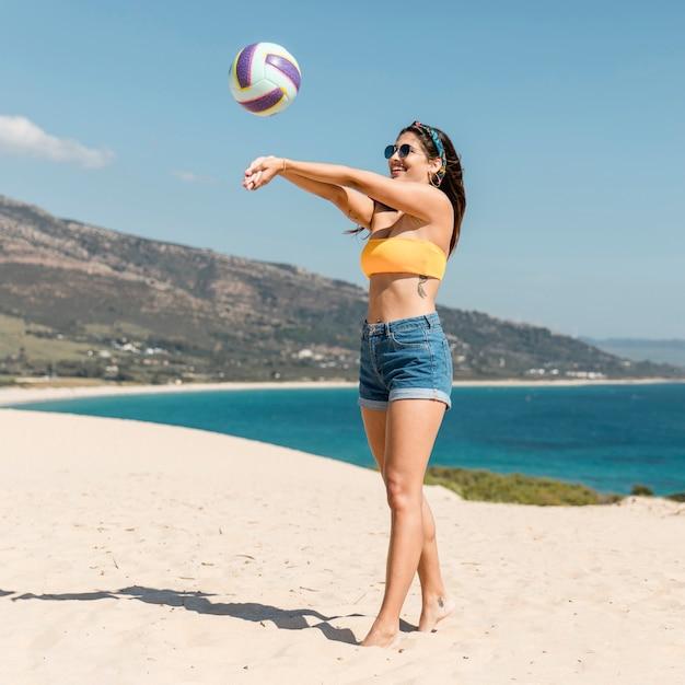Piękna Młoda Kobieta Bawić Się Siatkówkę Na Plaży Darmowe Zdjęcia