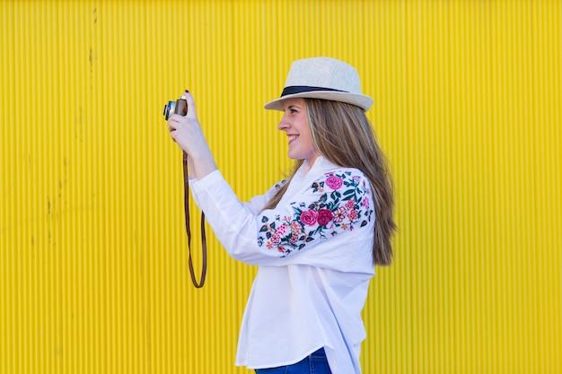 Piękna młoda kobieta bierze obrazek zi starą rocznik kamery koloru żółtego ścianą Premium Zdjęcia