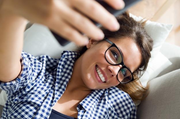 Piękna młoda kobieta bierze selfie w domu. Darmowe Zdjęcia