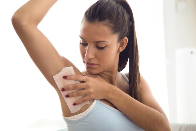 Piękna młoda kobieta goli jej pachę z woskiem w łazience. Darmowe Zdjęcia