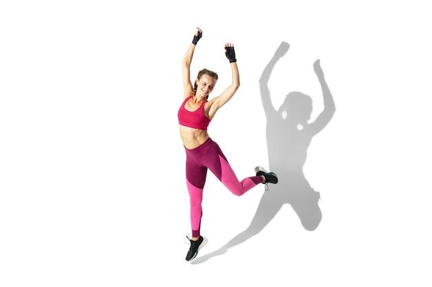 Piękna Młoda Kobieta Lekkoatletka ćwiczy Na Białej Przestrzeni, Portret Z Cieniami Darmowe Zdjęcia