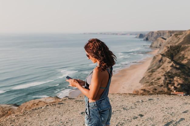 Piękna Młoda Kobieta Na Szczycie Wzgórza Używać Jej Telefon Komórkowego I Ono Uśmiecha Się. Czas Letni Styl życia Premium Zdjęcia
