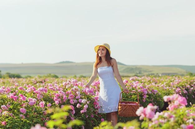 Piękna młoda kobieta pozuje blisko róż w ogródzie, Premium Zdjęcia