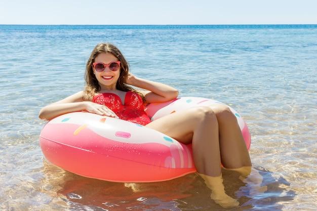Piękna młoda kobieta relaksuje w błękitnym morzu z nadmuchiwanym pierścionkiem Premium Zdjęcia