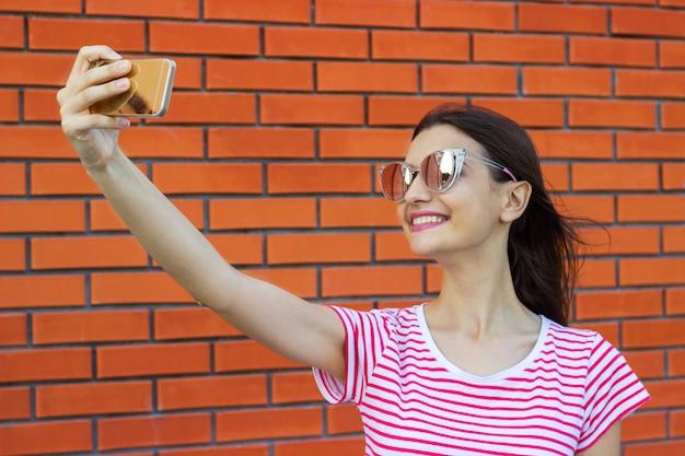 Piękna Młoda Kobieta Robi Autoportretowi Na Smartphone Na ściana Z Cegieł Premium Zdjęcia