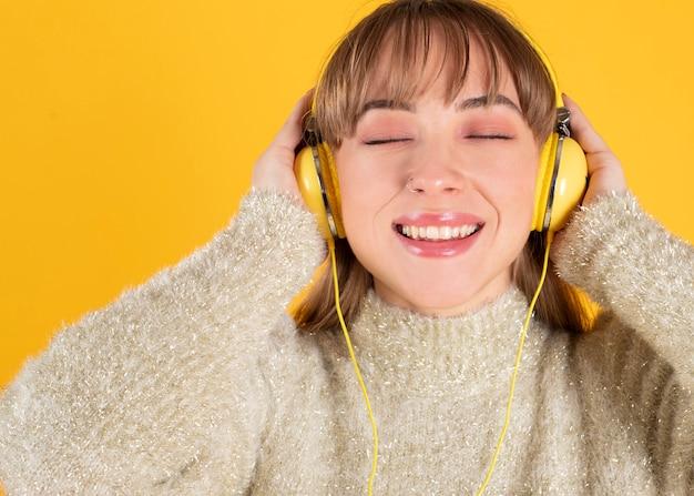 Piękna Młoda Kobieta Słucha Muzyki W Słuchawkach Z Zamkniętymi Oczami, żółte Tło Premium Zdjęcia