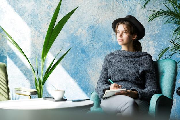 Piękna Młoda Kobieta Ubrana W Sweter I Kapelusz Siedzi Na Krześle Przy Stoliku Kawiarnianym, Robiąc Notatki Premium Zdjęcia