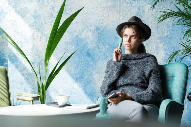 Piękna Młoda Kobieta Ubrana W Sweter I Kapelusz Siedzi Na Krześle Przy Stoliku Kawiarnianym, Rozmawia Przez Telefon Komórkowy, Stylowe Wnętrze Premium Zdjęcia