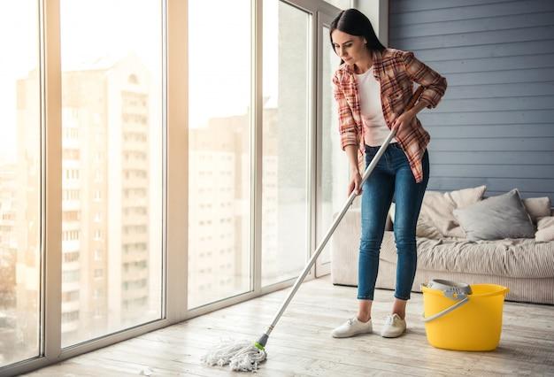 Piękna młoda kobieta uśmiecha się podczas czyszczenia podłogi Premium Zdjęcia