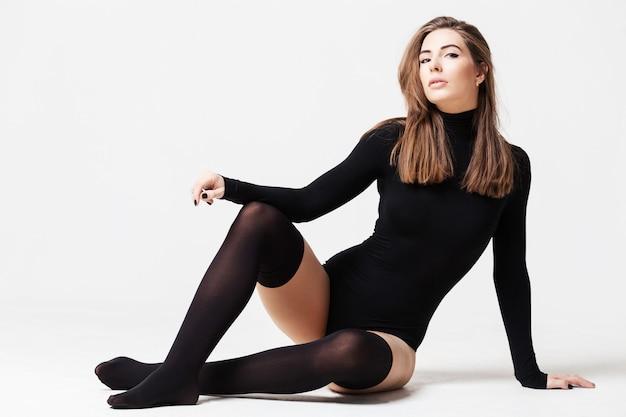 Piękna młoda kobieta w bieliźnie siedzi na podłodze Premium Zdjęcia