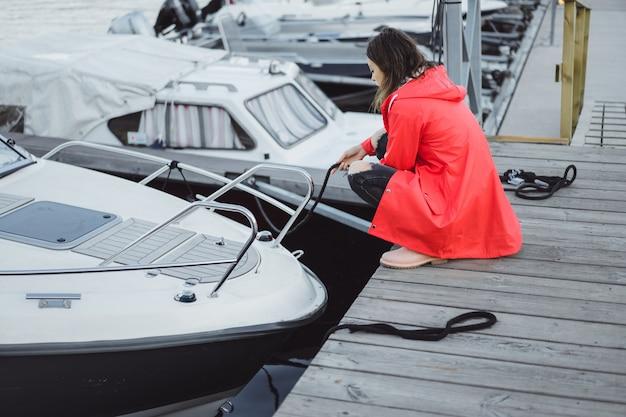 Piękna Młoda Kobieta W Czerwonej Pelerynie W Porcie Jachtowym. Sztokholm, Szwecja Darmowe Zdjęcia