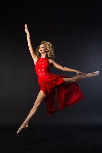 Piękna Młoda Kobieta W Czerwonej Sukience Skoki W Baletowej Pozie Na Czarnym Tle Premium Zdjęcia