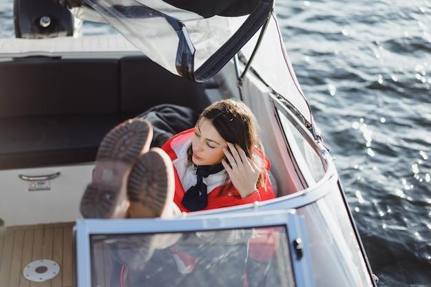 Piękna młoda kobieta w czerwonym płaszczu jeździ prywatnym jachtem. sztokholm, szwecja Darmowe Zdjęcia