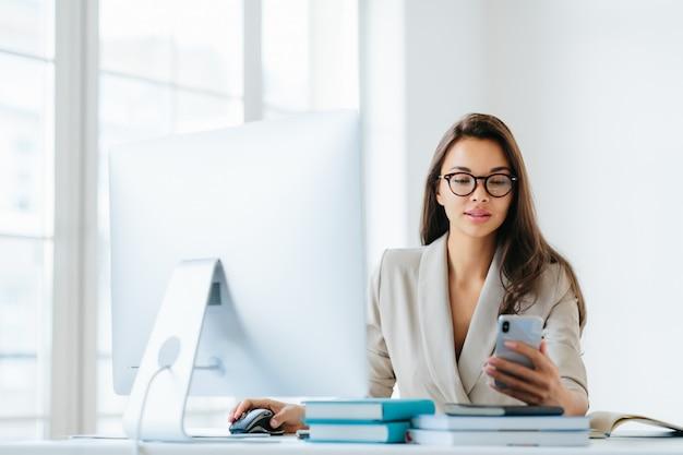 Piękna młoda kobieta w eleganckie ubrania sprawdza kanał informacyjny za pośrednictwem smartfona Premium Zdjęcia